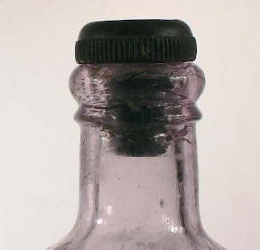 Image of an early 20th century ammonium bottle with an inside thread finish and hard rubber stopper; click to enlarge.